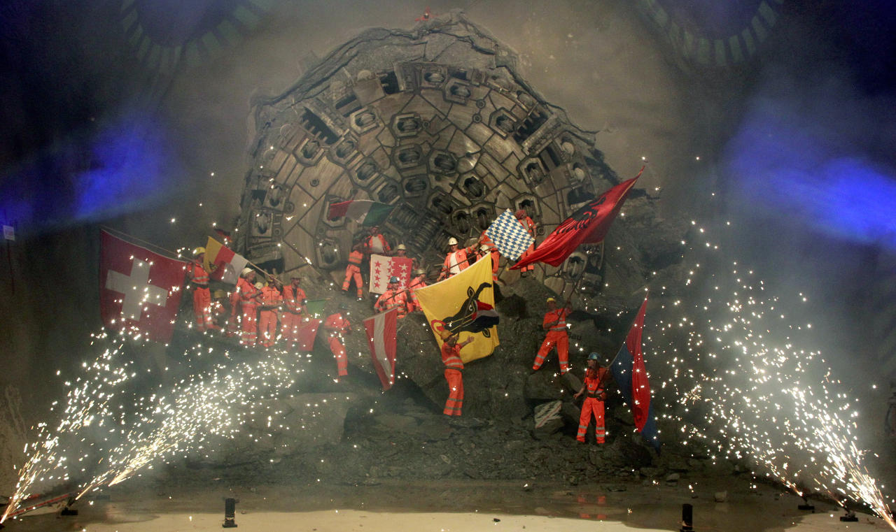 Miners celebrate as fireworks explode after a giant drill machine broke through the rock at the final section Sedrun-Faido, at the construction site of the NEAT Gotthard Base Tunnel March 23, 2011. Crossing the Alps, the world's longest train tunnel should become operational at the end of 2016. The project consists of two parallel single track tunnels, each of a length of 57 km (35 miles).  REUTERS/Arnd Wiegmann (SWITZERLAND - Tags: BUSINESS TRAVEL EMPLOYMENT) - RTR2KAQD