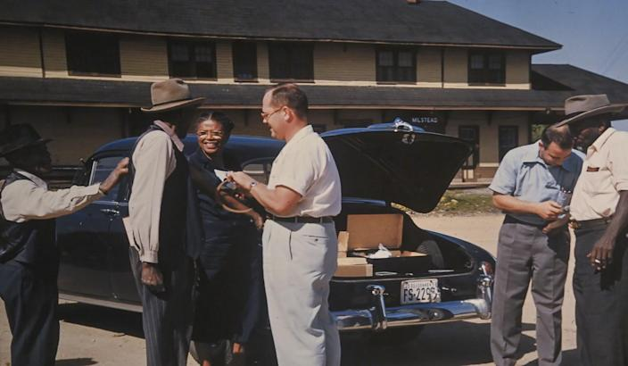 Government officials and residents stand next to a car.