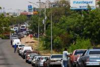 FILE PHOTO: People with vehicles wait in line in an attempt to refuel at a gas station of the state oil company PDVSA in Maracaibo