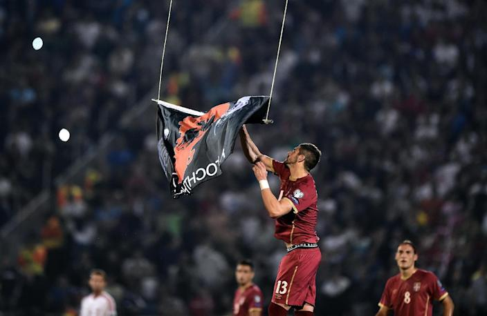Serbia's Stefan Mitrovic grabs a flag with Albanian national symbols flown by a remotely operated drone during the Euro 2016 qualifying football match between Serbia and Albania in Belgrade on October 14, 2014 (AFP Photo/Andrej Isakovic)