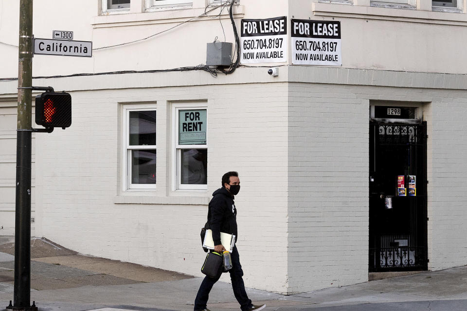 A pedestrian passes under for rent and for lease signs in San Francisco on Wednesday, Oct. 21, 2020. As the coronavirus pandemic transforms San Francisco's workplace, legions of tech workers have left, able to work remotely from anywhere. Families have fled for roomy suburban homes with backyards. The exodus has pushed rents in the prohibitively expensive city to their lowest in years. (AP Photo/Noah Berger)