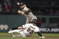 San Diego Padres shortstop Fernando Tatis Jr., top, throws to first base after forcing San Francisco Giants' Kris Bryant (23) out at second base during the fourth inning of a baseball game in San Francisco, Wednesday, Sept. 15, 2021. (AP Photo/Jeff Chiu)