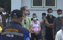 An immigration officer stand beside a group of foreigners in front of police station to attend a court hearing through video conferencing on Koh Phangan island, Surat Thani province, southern Thailand, Thursday, Jan. 28, 2021. An illicit party in a bar on the popular island ended in a mass legal hangover on Thursday when a court handed out jail terms and fines to more than a hundred revelers for breaking national COVID restrictions. (AP Photo)