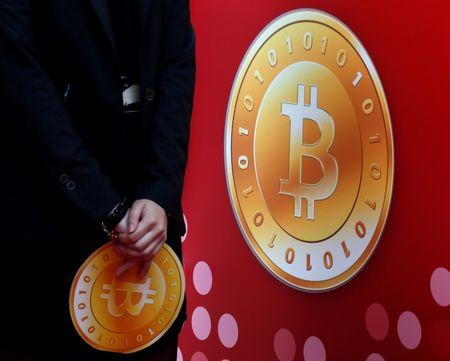 FILE PHOTO: Attendant holds bitcoin sign during the opening of Hong Kong's first bitcoin retail store