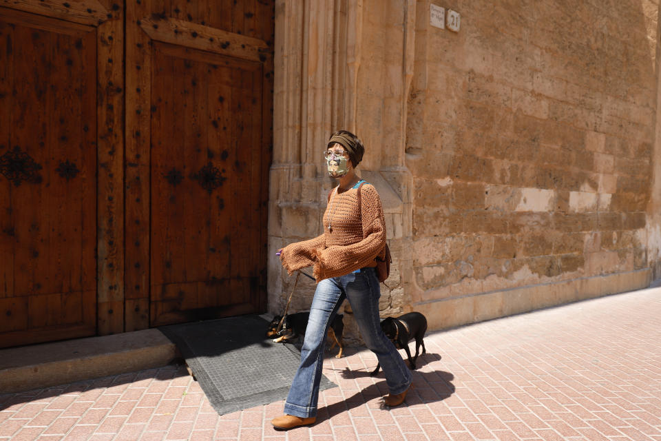 09 April 2020, Spain, Palma de Mallorca: Antonia wears a self-made protective mask while she walks her dogs. In the fight against the coronavirus pandemic, severely affected Spain is making further progress. Photo: Clara Margais/dpa (Photo by Clara Margais/picture alliance via Getty Images)