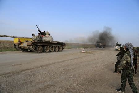 A military tank is driven past Kurdish People's Protection Units (YPG) and Kurdistan Workers Party (PKK) fighters manning a checkpoint on a highway connecting the Iraqi-Syrian border town of Rabia and the town of Snuny, north of Mount Sinjar December 20, 2014.  REUTERS/Massoud Mohammed