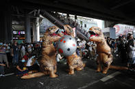 "Dinosaur mascots hold a large ball depicting an asteroid during a student rally in Bangkok, Saturday, Nov. 21, 2020. Organized by a group that mockingly calls themselves ""Bad Students,"" the rally calls for educational reforms and also supports the broader pro-democracy movement's demands for constitutional change. (AP Photo/Sakchai Lalit)"