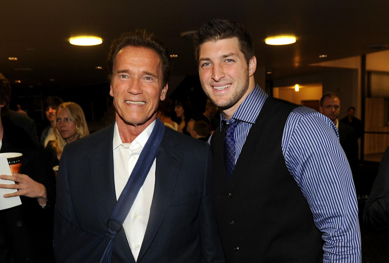 """HOLLYWOOD, CA - FEBRUARY 13:  Former Governor of California Arnold Schwarzenegger (L) and NFL Player Tim Tebow of the Denver Broncos arrive at the premiere of Relativity Media's """"Act Of Valor"""" held at ArcLight Cinemas on February 13, 2012 in Hollywood, California.  (Photo by Jason Merritt/Getty Images for Relativity Media)"""