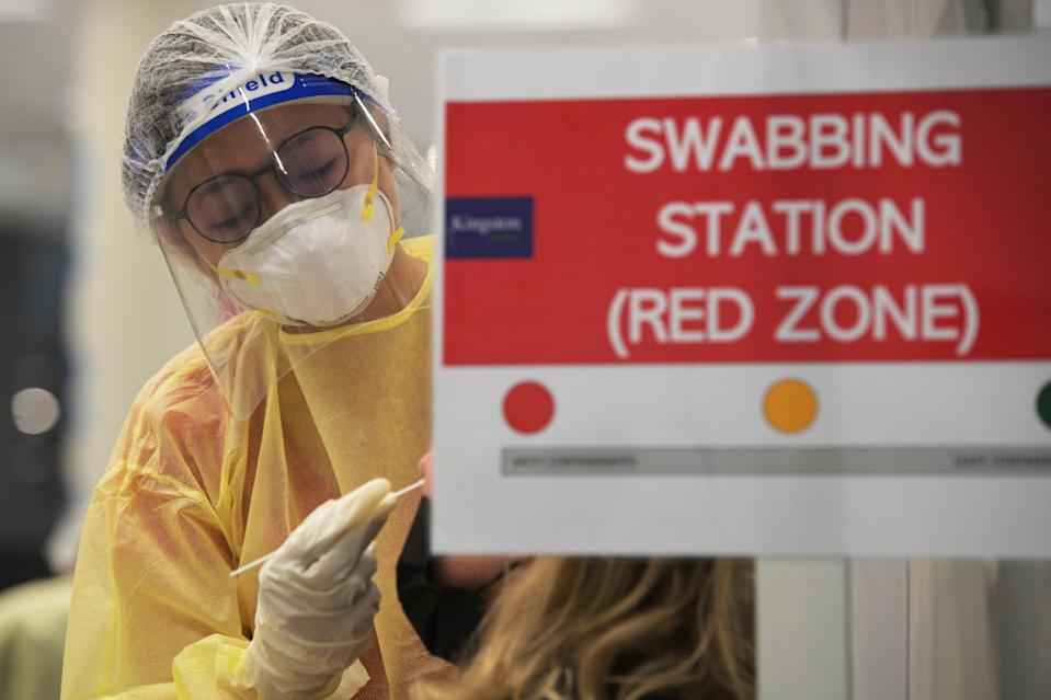 A medical worker takes a swab sample from a spectator for a COVID-19 test before the Singapore Tennis Open semifinal in Singapore on 27 February, 2021. (PHOTO: Xinhua via Getty Images)