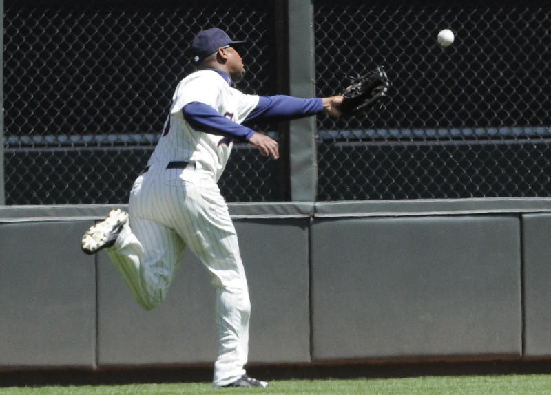 Minnesota Twins left fielder Delmon Young reaches in vain for a long fly ball off the bat of Toronto Blue Jays ' Aaron Hill who had a two-run double on the play in the first inning of a baseball game Sunday, May 15, 2011 in Minneapolis.  (AP Photo/Jim Mone)