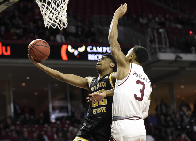 Wichita State's Grant Sherfield (52) drives to the basket past Temple's Josh Pierre-Louis (3) during the first half of an NCAA college basketball game Wednesday, Jan. 15, 2020, in Philadelphia. (AP Photo/Michael Perez)