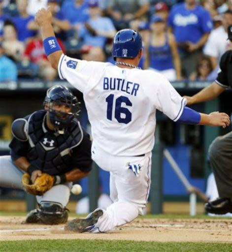 Kansas City Royals' Billy Butler (16) scores as the ball gets past Atlanta Braves catcher Gerald Laird (11) during the first inning of a baseball game at Kauffman Stadium in Kansas City, Mo., Wednesday, June 26, 2013. (AP Photo/Orlin Wagner)