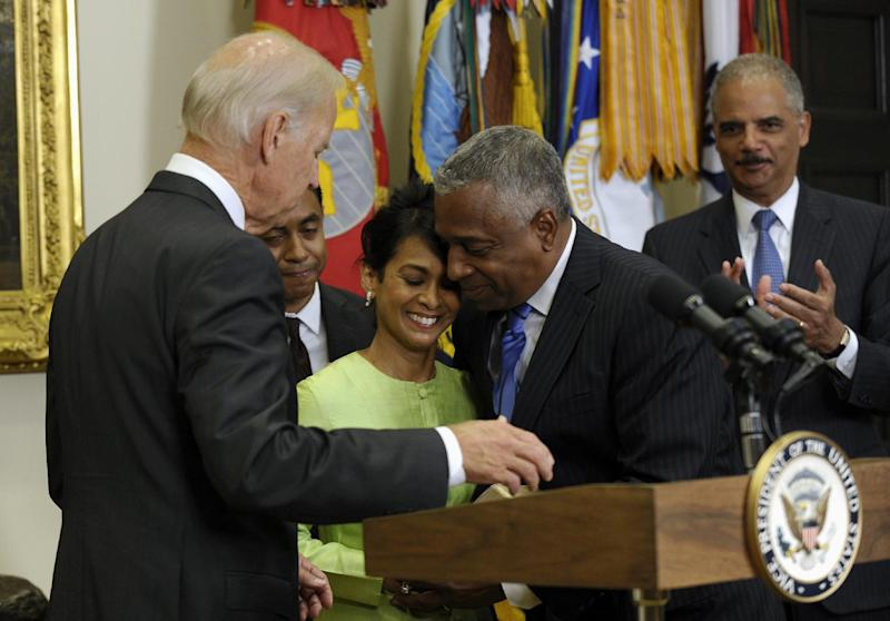 Vice President Biden and Attorney General Eric Holder, right, watch as Bureau of Alcohol, Tobacco, and Firearms (ATF) Director Todd Jones, center, hugs his wife Margaret, accompanied by their son Anthony, after he was ceremonial swearing-in for Jones, Thursday, Aug. 29, 2103, in the Roosevelt Room of the White House in Washington. (AP Photo/Susan Walsh)