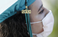 """FILE - In this June 23, 2020, file photo, Valedictorian Sierra Morgado's graduation tassel has """"2020"""" on it as she listens during a graduation ceremony for the senior class of Chambers High School at Homestead-Miami Speedway in Homestead, Fla. (AP Photo/Wilfredo Lee)"""