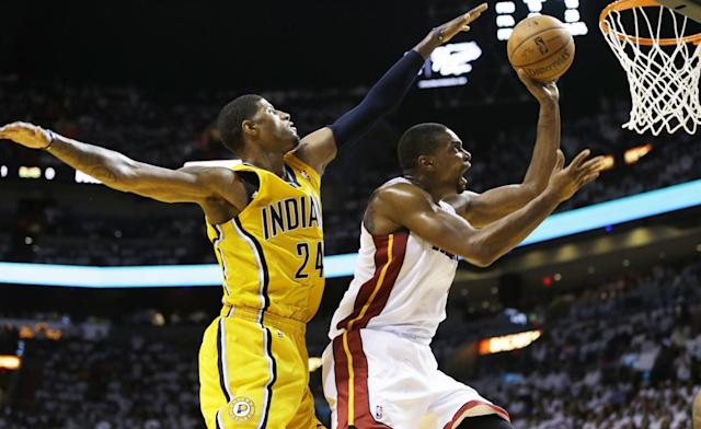 Miami Heat center Chris Bosh (1) drives to the basket as Indiana Pacers forward Paul George (24) defends during the second half of Game 3 in the NBA basketball Eastern Conference finals playoff series, Saturday, May 24, 2014, in Miami. The Heat defeated the Pacers 99-87. (AP Photo/Lynne Sladky)