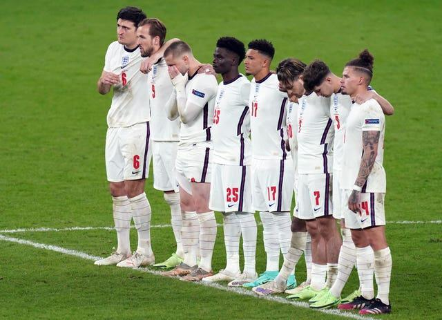 England's Jadon Sancho  and Bukayo Saka stand alongside their team-mates during the penalty shoot-out