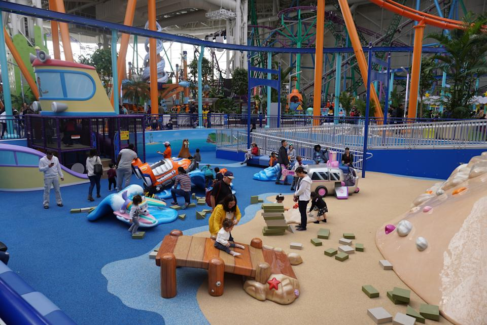 Toddlers play with their parents in an exploratory jungle gym at Nickelodeon Universe.