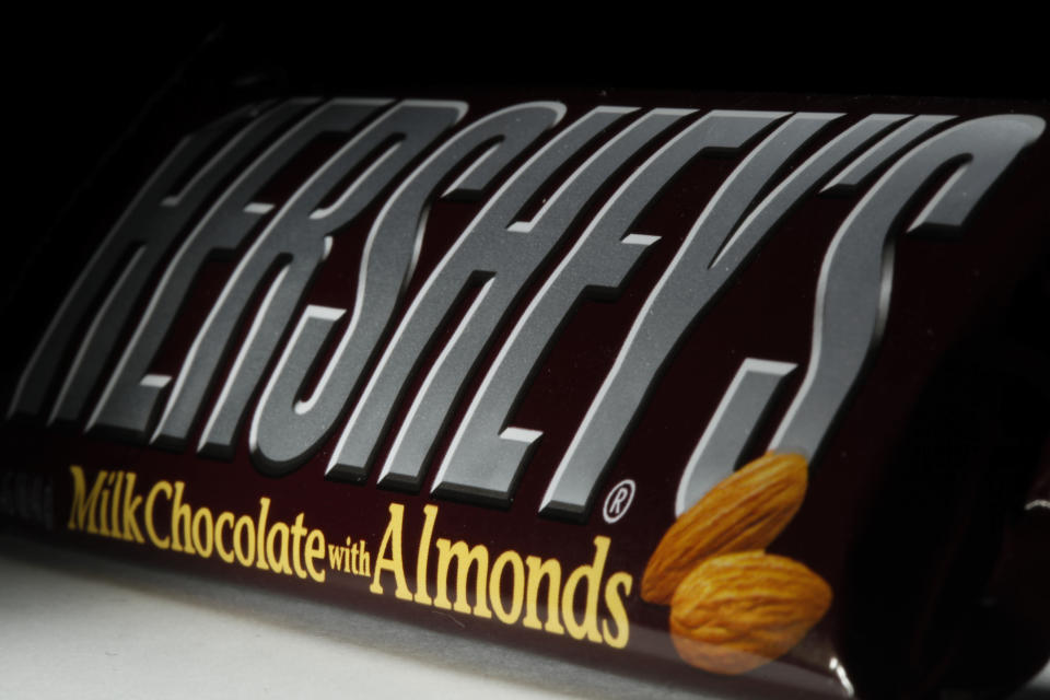 FILE - This April 21, 2020 file photo shows a Hershey's chocolate bar with almonds in Philadelphia. Hershey says its Halloween candy sales were up slightly this year despite lower enthusiasm for trick-or-treating amid the pandemic. Michele Buck _ chairman, president and CEO of The Hershey Co. _ said Friday, Nov. 6, 2020, that earlier shipments of Halloween candy to stores helped boost sales. (AP Photo/Matt Rourke, File)