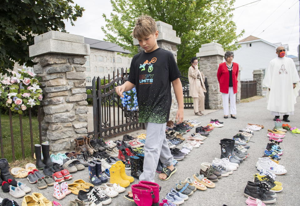 Jamieson Kane puts down tobacco as a tribute to all the victims of the residential school system as he walks amongst children's shoes outside St. Francis Xavier Church in Kahnawake, Quebec, Sunday, May 30, 2021. (Graham Hughes/The Canadian Press via AP)