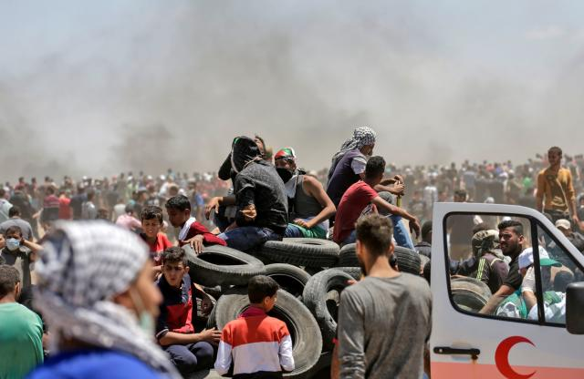 <p>Palestinian men bring tires to be burned during clashes with Israeli forces near the border between the Gaza Strip and Israel, east of Gaza City, on May 14, 2018, as Palestinians protest the inauguration of the U.S. Embassy following its controversial move to Jerusalem. (Photo: Mahmud Hams/AFP/Getty Images) </p>