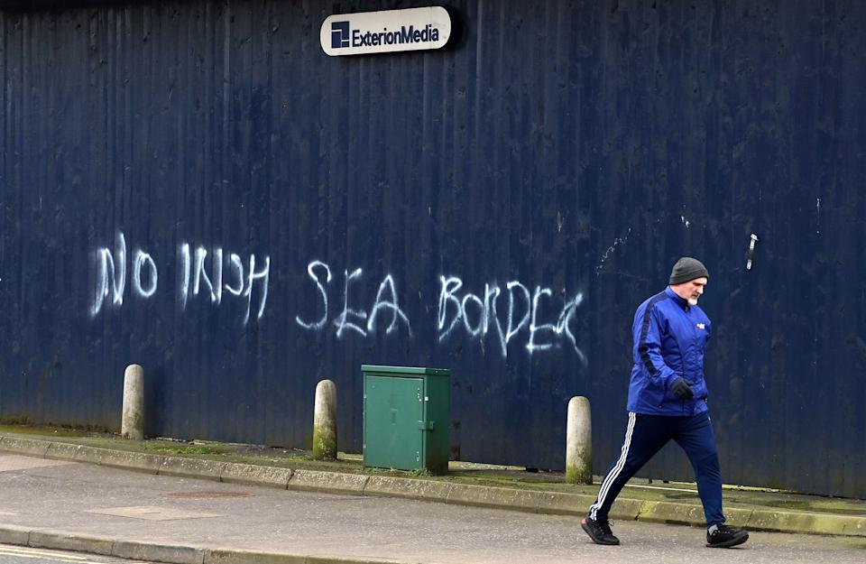 BELFAST, NORTHERN IRELAND - JANUARY 31: A man walks past freshly painted loyalist graffiti in Belfast city centre on January 31, 2021 in Belfast, Northern Ireland. The Police Service of Northern Ireland has said it has been monitoring growing unionist discontent regards the implementation of a so called Irish sea border and comes as the EU reversed its decision to invoke Article 16 of the Brexit withdrawal agreement to control the export of coronavirus vaccines from the EU into NI. Northern Ireland's first minister and leader of the main unionist party, the DUP, Arlene Foster said the move to trigger Article 16 of the NI Protocol was an act of hostility. The EU countries are experiencing a huge shortfall in vaccines and there was concern the Irish border could be used as a backdoor for supplies entering the UK. (Photo by Charles McQuillan/Getty Images)