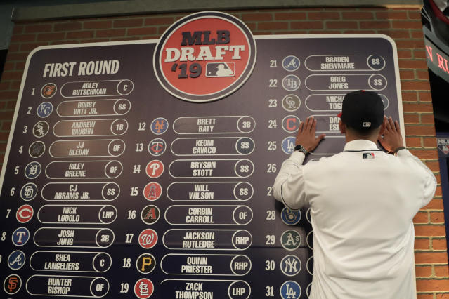 FILE - In this June 3, 2019, file photo, Daniel Espino, a right-handed pitcher from Georgia Premier Academy in Statesboro, Ga., places his name on the draft board after being selected No. 24 by the Cleveland Indians in the first round of the baseball draft in Secaucus, N.J. Baseballs amateur draft this week will look much different because of the coronavirus pandemic, and more permanent changes could be coming soon. (AP Photo/Julio Cortez, File)