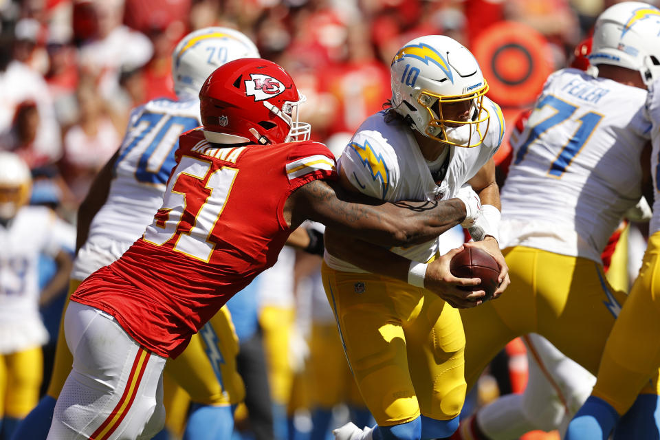 KANSAS CITY, MISSOURI - SEPTEMBER 26: Justin Herbert #10 of the Los Angeles Chargers is tackled by Michael Danna #51 of the Kansas City Chiefs during the second half at Arrowhead Stadium on September 26, 2021 in Kansas City, Missouri. (Photo by David Eulitt/Getty Images)