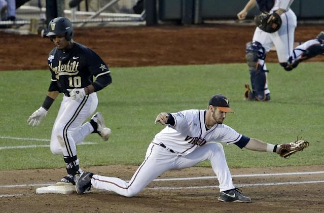 Vanderbilt's John Norwood (10) arrives at first with a single sd Virginia first baseman Mike Papi misses the throw during the sixth inning of Game 3 of the best-of-three NCAA baseball College World Series finals in Omaha, Neb., Wednesday, June 25, 2014. Norwood advanced to second base. (AP Photo/Nati Harnik)