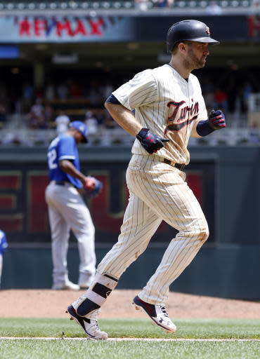 Minnesota Twins' Brian Dozier jogs home after hitting a two-run home run off Kansas City Royals reliever Enny Romero, left, in the sixth inning of a baseball game Wednesday, July 11, 2018, in Minneapolis. (AP Photo/Jim Mone)
