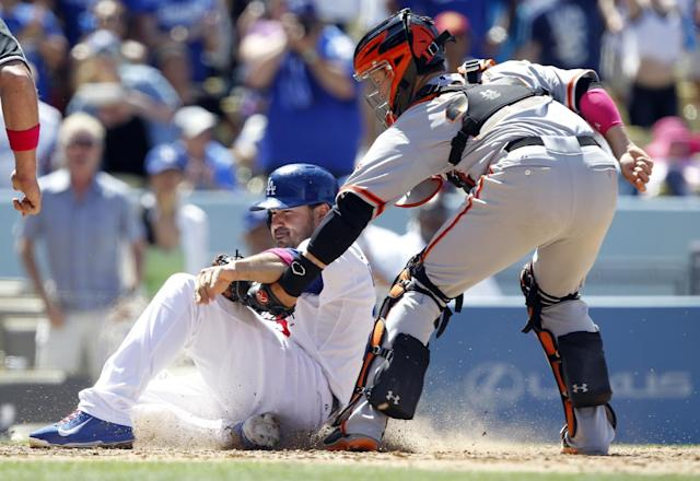 San Francisco Giants catcher Buster Posey, right, tags out Los Angeles Dodgers' Adrian Gonzalez trying to score from second base on a single to center field in the sixth inning of a baseball game on Sunday, May 11, 2014, in Los Angeles. (AP Photo/Alex Gallardo)