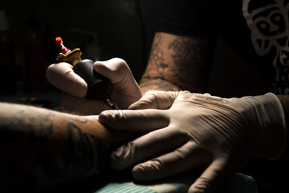 Midsection Of Man Tattooing On Hand