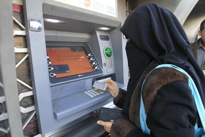 A Palestinian woman withdraws money from an ATM machine in Gaza City on December 7, 2011 (AFP Photo/Mohammed Abed)