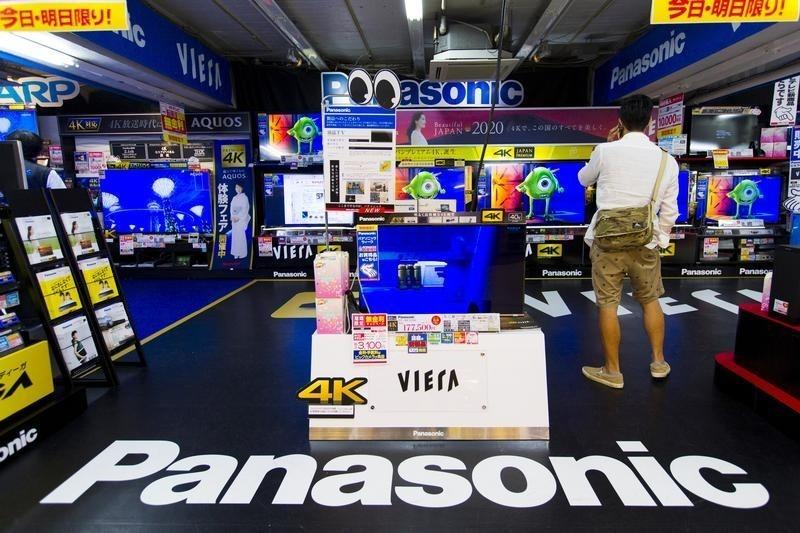 A man looks at television sets by Japanese firm Panasonic at an electronics retailer in Tokyo