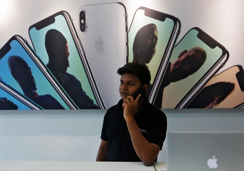 Salesperson speaks on the phone at an Apple reseller store in Mumbai