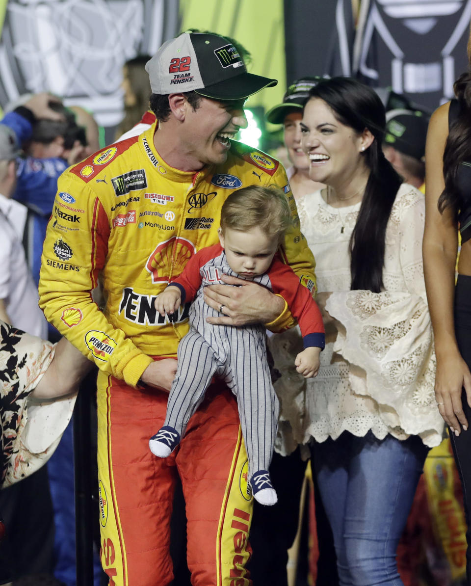Joey Logano stands with his wife Brittany Baca, as he holds their son Hudson, after winning the NASCAR Cup Series Championship auto race at the Homestead-Miami Speedway, Sunday, Nov. 18, 2018, in Homestead, Fla. (AP)