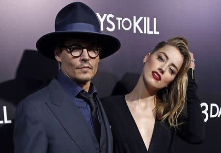 "Cast member Amber Heard and her fiance, actor Johnny Depp, pose at the premiere of ""3 Days to Kill"" in Los Angeles"