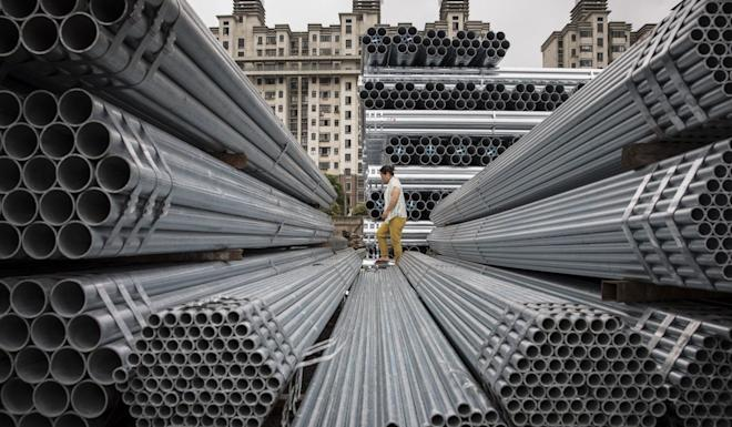 A worker walks over bundles of steel pipe stacked at a stockyard on the outskirts of Shanghai. Photo: Bloomberg
