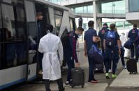 England cricketer Chris Woakes, center with black suitcase, walks after arriving with teammates at Mattala Rajapaksa International airport in Hambantota, Sri Lanka, Sunday, Jan. 3, 2021. Team allrounder Moeen Ali was isolating in Sri Lanka on Monday after testing positive for the coronavirus upon his arrival in the South Asian country for the team's two-test cricket tour. Woakes has been deemed as a possible close contact of Ali and was also observing a period of self-isolation in developments which have cast an early shadow on the tour that takes place weeks after a white-ball trip to South Africa was derailed by a spate of positive COVID-19 results. (AP Photo/Nuwan Jayasekara)
