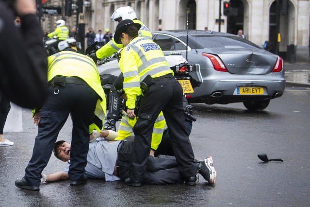Police detain a man after he ran in front of Boris Johnson's car. (Victoria Jones/PA Images via Getty Images)