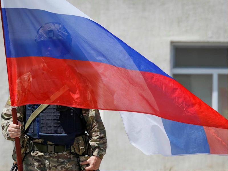 A member of Russia's special operations unit stands with a national flag. In June the US Treasury imposed sanctions on Russia for suspected cyber attacks. (REUTERS/Shamil Zhumatov)