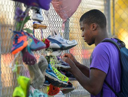 Darrell Ugboaga, 16, hangs his running shoes on a memorial for Trinity Gay, the daughter of Olympic sprinter Tyson Gay, who died in an exchange of gunfire early Sunday morning, in Lexington, Kentucky, October 17, 2016. REUTERS/Bryan Woolston