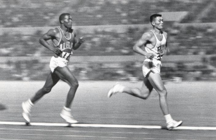 Rafer Johnson of the United States competes against Yang Chuan-kwang of China in the 1,500-meters portion of the decathlon.