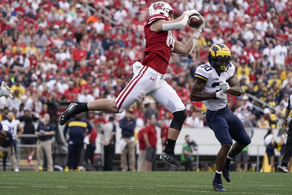Wisconsin's Jake Ferguson catches a pass in front of Michigan's Daxton Hill during the first half of an NCAA college football game Saturday, Oct. 2, 2021, in Madison, Wis. (AP Photo/Morry Gash)