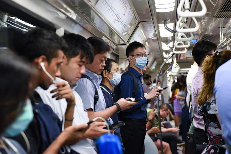 Commuters wear face masks on the Mass Rapid Transit train as a preventive measure against the COVID-19 coronavirus in Singapore on March 18, 2020. (Photo by Catherine LAI / AFP) (Photo by CATHERINE LAI/AFP via Getty Images)
