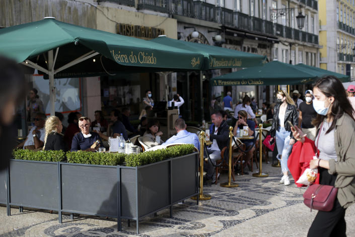 People sit a cafe terrace in downtown Lisbon, Friday, June 4, 2021. Britain said Thursday that it is removing Portugal from its list of COVID-safe travel destinations, meaning thousands of U.K. residents currently on vacation there face the prospect of 10 days' quarantine on return. (AP Photo/Armando Franca)
