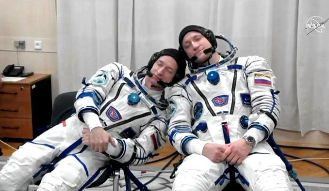 Calm cosmonauts? Commander Sergey Ryzhikov, left, and flight engineer Sergey Kud-Sverchkov take a quick nap -- or pretend to -- during suit-up before launch.  / Credit: NASA/Roscosmos