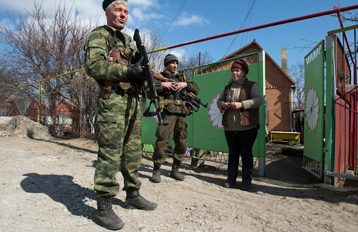 Soldiers of the self-proclaimed Donetsk People's Republic (DNR) speak to a resident in the frontline town of Shyrokyne, some 10 kms east of Mariupol, on March 20, 2015 (AFP Photo/John MacDougall)