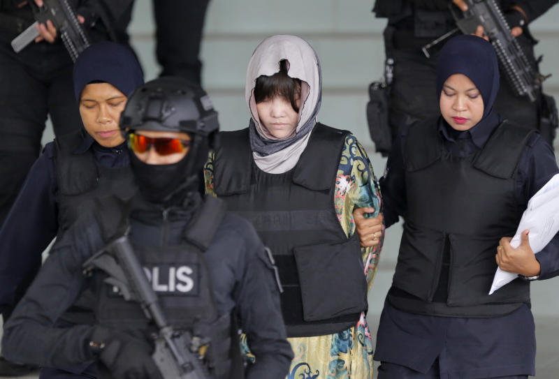 In this Aug. 16, 2018, photo, Vietnamese Doan Thi Huong, center, is escorted by police as she leaves her court hearing at the Shah Alam High Court in Shah Alam, Malaysia. The Malaysian court has ordered the two women, Doan Thi Huong and Indonesian Siti Aisyah to enter their defense over the murder of North Korean leader's half-brother in a brazen assassination that has gripped the world. (AP Photo/Yam G-Jun, File)