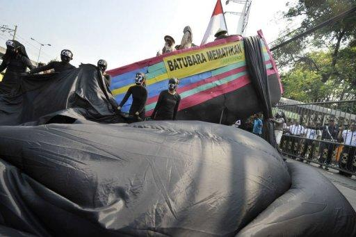 """Greenpeace activists wearing black suits stand beside a symbolic boat (top) with a banner that reads """"coal kills"""""""