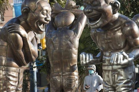 A woman wears a face mask as she walks past statues at English Bay in Vancouver on Tuesday. Photo: AP